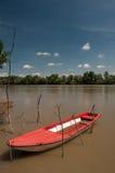 Barco plástico rojo que flota en el río Fotografía de archivo