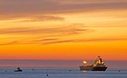 Barco por el mar en la puesta del sol Fotografía de archivo