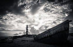 Barco por un faro Imagenes de archivo