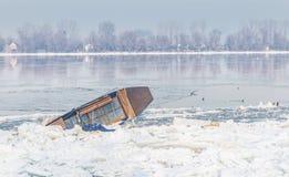 Barco prendido no banco do rio congelado Danúbio Imagem de Stock