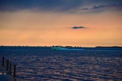 Barco que apresura en la puesta del sol imagenes de archivo