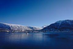 Barco que conduce a través del agua con las montañas de la nieve detrás imágenes de archivo libres de regalías