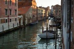 Barco que descansa una puesta del sol a lo largo de un canal en Venecia, Italia Imagen de archivo libre de regalías