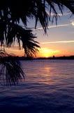 Barco que dirige a casa en la puesta del sol Foto de archivo