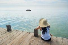 Barco que espera de la mujer para en el muelle Imagen de archivo libre de regalías