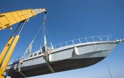 Barco que está sendo levantado pela maquinaria pesada do guindaste Fotografia de Stock