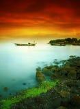 Barco que flota debajo del cielo rojo nublado Fotos de archivo libres de regalías