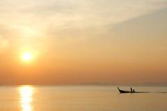 Barco que flota en el mar en la puesta del sol Fotografía de archivo