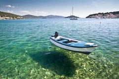 Barco que flota en las aguas cristalinas, Tisno, Croacia fotos de archivo