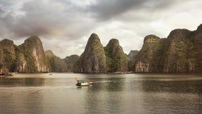 Barco que pasa delante de las colinas místicas en la bahía de Halong imagen de archivo libre de regalías