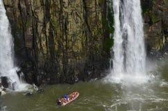 Barco que practica los deportes extremos, cascada gigante, paisaje hermoso entre las rocas Imagen de archivo libre de regalías