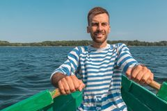 Barco que rema del hombre joven a través del lago en verano foto de archivo