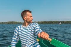 Barco que rema del hombre joven a través del lago en verano foto de archivo libre de regalías