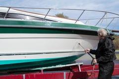 Barco que se lava del hombre con la lavadora de la presión Imagenes de archivo