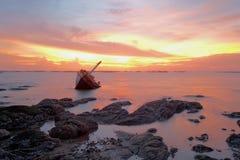 Barco quebrado no mar no crepúsculo Fotos de Stock