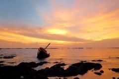 Barco quebrado no mar no tempo crepuscular Fotos de Stock