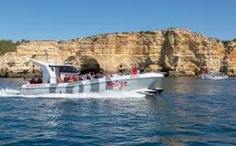 Barco rápido de Portimao que toma turistas em torno da costa perto de Carvoeiro para visitar as cavernas Fotografia de Stock Royalty Free