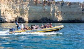 Barco rápido do reforço que toma turistas em torno da costa perto de Carvoeiro para visitar as cavernas Fotografia de Stock
