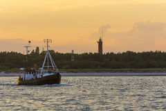 Barco rastreador con los turistas que pasan el faro de los Hel Imagen de archivo libre de regalías