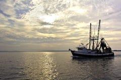 Barco rastreador de la pesca en el agua en la salida del sol Foto de archivo libre de regalías