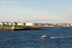 Barco rastreador más allá de depósitos de gasolina Imagen de archivo