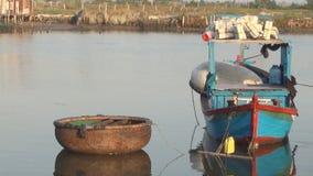 Barco redondo vietnamita de la cesta y barco de pesca anclado en el río metrajes