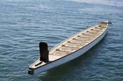 Barco a remos acima amarrado no mar azul Fotos de Stock