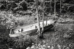 Barco a remos levantado no banco pela água Fotos de Stock