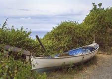 Barco a remos quebrado e abandonado pelo oceano imagens de stock