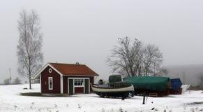 Barco rojo de la niebla del invierno de la cabaña Foto de archivo libre de regalías