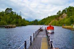 Barco rojo en un muelle del puerto en un lago famoso en Escocia: Lago Kat imagenes de archivo
