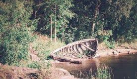 Barco roto abandonado en el río Foto teñida Fotografía de archivo
