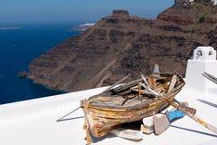 Barco roto de madera viejo en el tejado de la casa, situado en la isla de Santorini, Grecia imagen de archivo