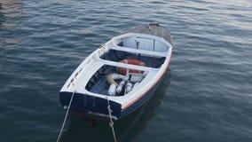 Barco só com o equipamento de pesca que flutua na água amarrada pela corda à amarração filme