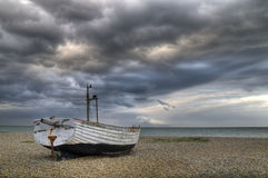 Barco só na praia sob um céu tormentoso Foto de Stock