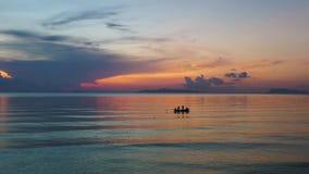 Barco solo de los pescadores en la cantidad del abejón de la puesta del sol metrajes