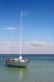 Barco solo en el mar en el fondo de nubes Foto de archivo