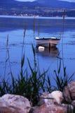 Barco solo en el río azul Imágenes de archivo libres de regalías