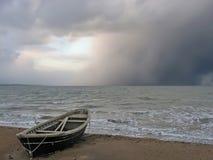 Barco solo en la orilla de un mar tempestuoso Imagen de archivo