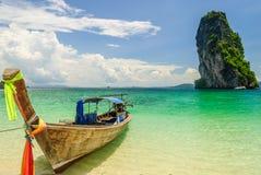 Barco tailandés de la cola larga que flota la isla próxima con la roca grande Foto de archivo libre de regalías
