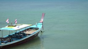 Barco tailandés del longtail que pasa a turistas de la espera en el mar en la playa tropical, de la costa de Phuket Tailandia almacen de metraje de vídeo