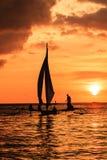 Barco tradicional en silueta contra un sol poniente Fotos de archivo libres de regalías