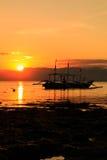 Barco tradicional en silueta contra un sol poniente Fotografía de archivo