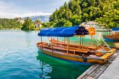 Barco turístico de madera en orilla del lago sangrado, Eslovenia Fotos de archivo libres de regalías
