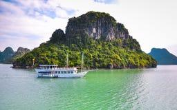 Barco turístico en el fondo de la isla rocosa verde Imagen de archivo libre de regalías