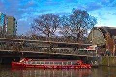Barco turístico parqueado en el río de Amsterdam Imagenes de archivo