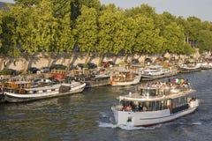 Barco turístico y lanchas a remolque en el río Seine Fotos de archivo