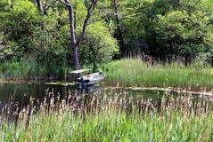 Barco usado velho ao lado da doca de madeira na lagoa Fotos de Stock