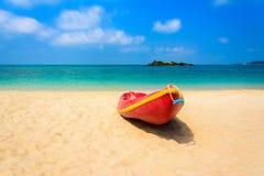 Barco vermelho na praia com mar azul e o céu azul Foto de Stock