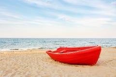 Barco vermelho velho na praia, ondas na água e fundo das nuvens Imagens de Stock Royalty Free